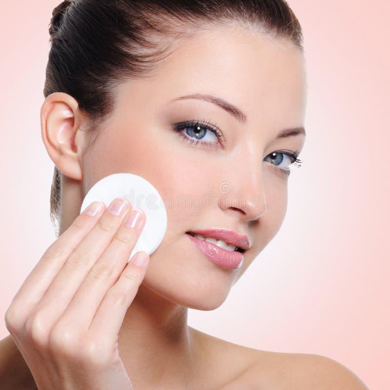 Frau, die ihr Gesicht mit Wattestäbchen säubert lizenzfreies stockbild