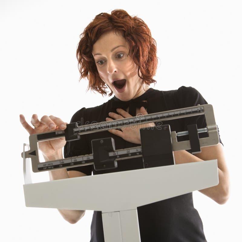 Frau, die ihr Gewicht überprüft lizenzfreies stockfoto