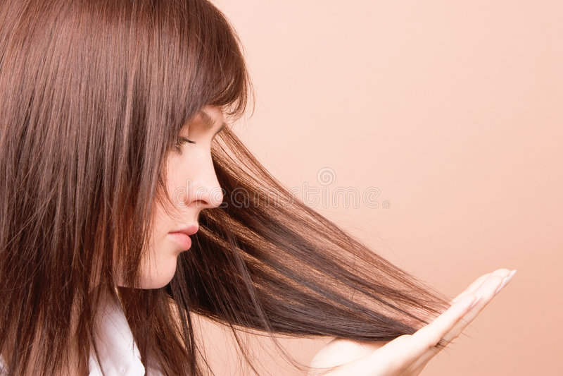 Frau, die ihr Haar berührt stockbild