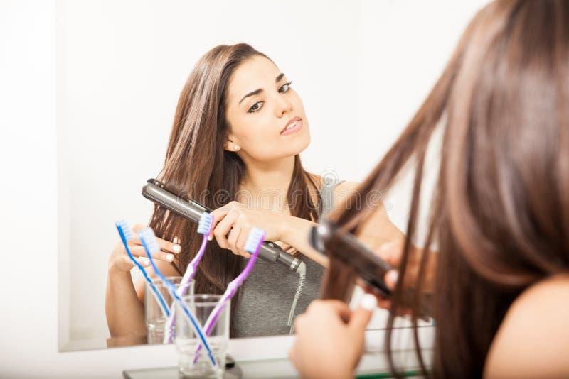 Frau, die ihr Haar geraderichtet lizenzfreie stockfotos