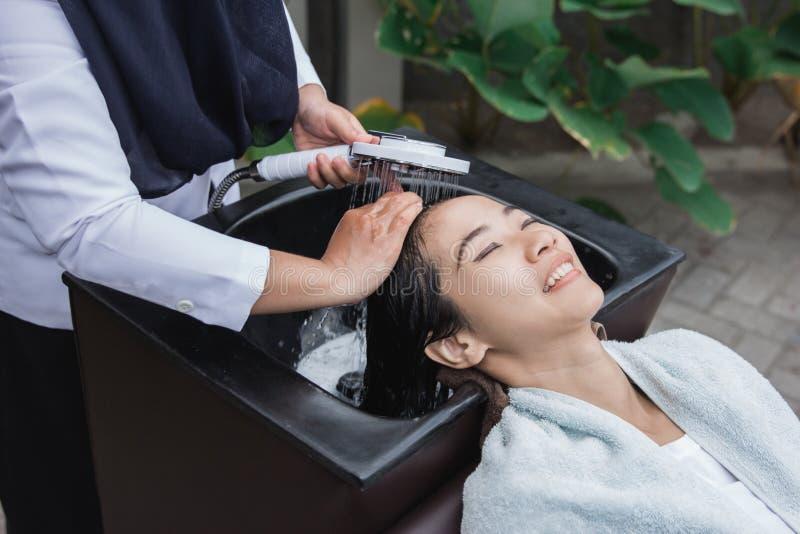 Frau, die ihr Haar gewaschen erhält lizenzfreies stockbild