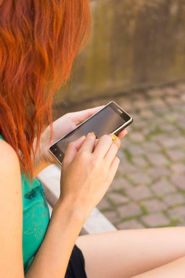 Frau, die ihr intelligentes Telefon verwendet lizenzfreies stockfoto