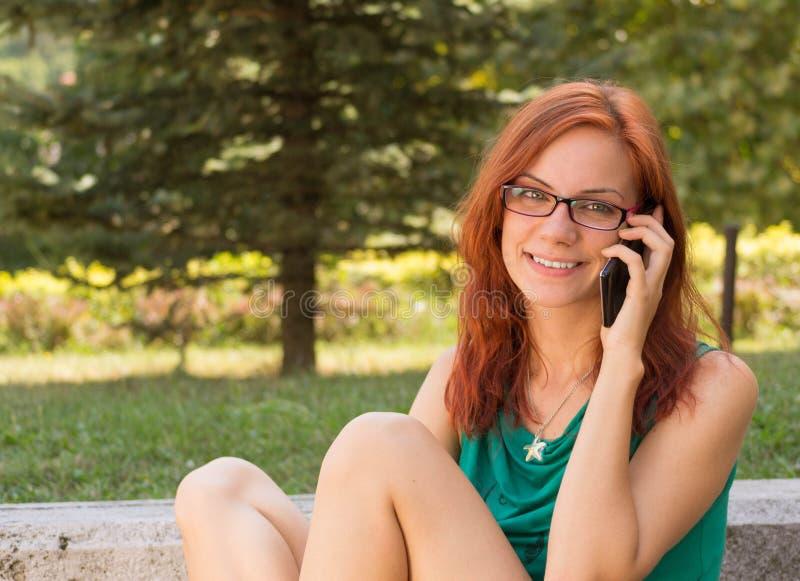 Frau, die ihr intelligentes Telefon verwendet lizenzfreie stockfotos