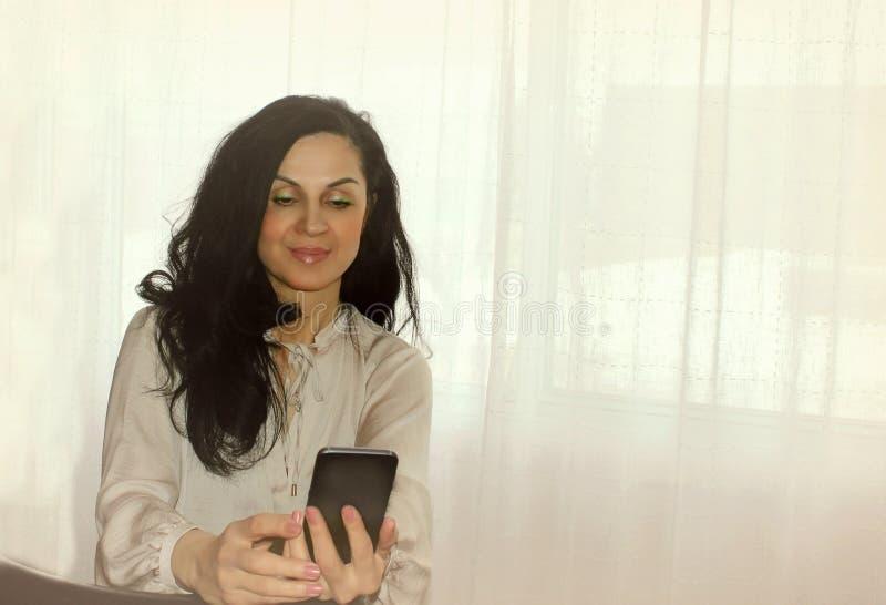Frau, die ihr intelligentes Telefon verwendet stockfotografie