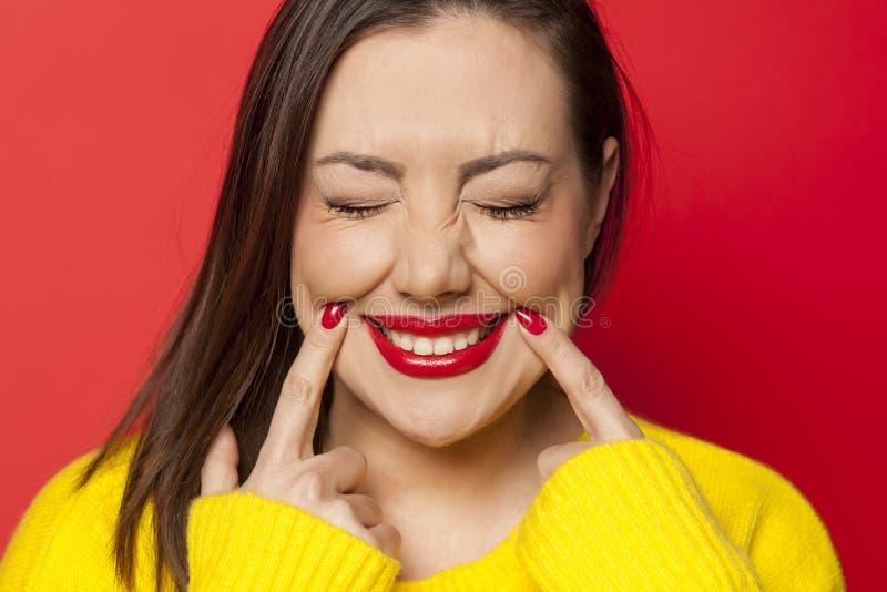 Frau, die ihr Lächeln zwingt lizenzfreies stockfoto