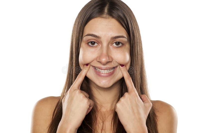 Frau, die ihr Lächeln zwingt lizenzfreie stockbilder