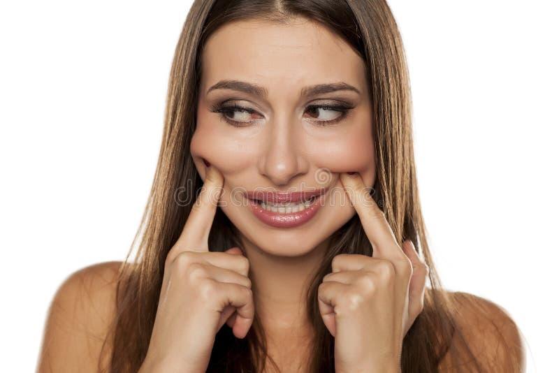 Frau, die ihr Lächeln zwingt lizenzfreie stockfotos