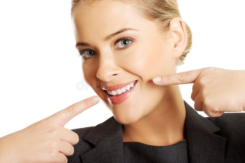Frau, die ihr perfekte weiße Zähne zeigt stockfotografie