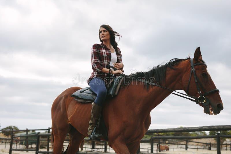 Frau, die ihr Pferd in der Hürde reitet stockfoto