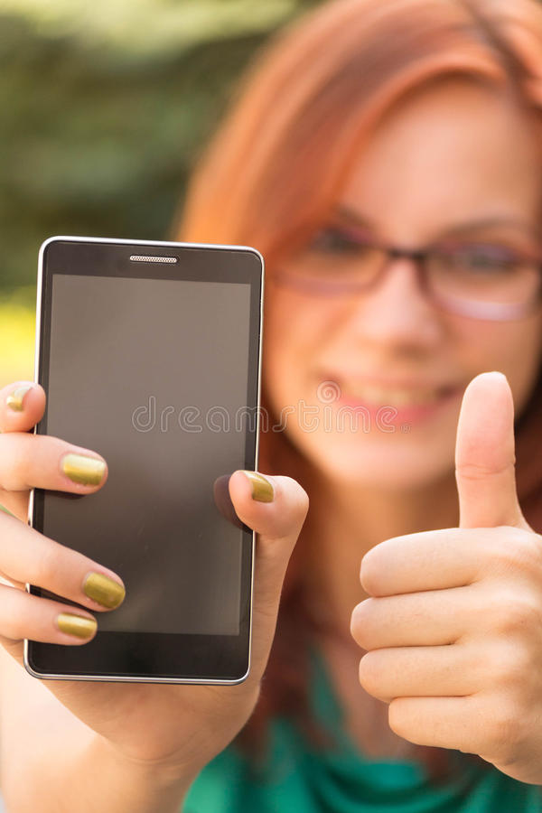 Frau, die ihr Smarttelefon zeigt stockfoto
