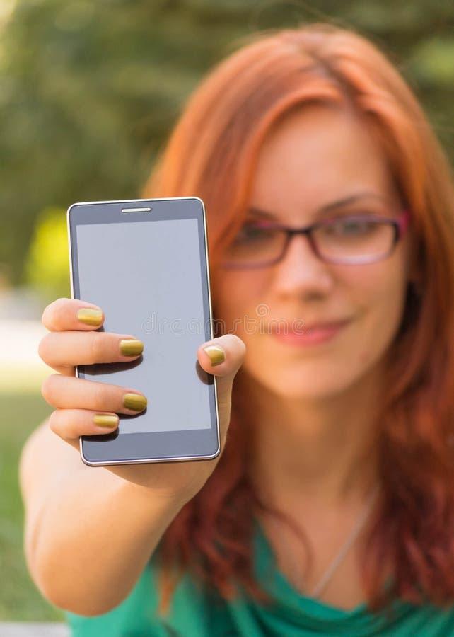 Frau, die ihr Smarttelefon zeigt stockfotos