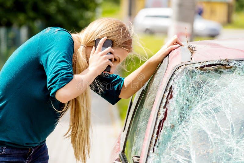 Frau, die ihr Telefon nach Autounfall wählt lizenzfreie stockbilder