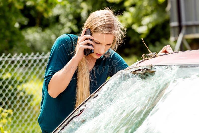 Frau, die ihr Telefon nach Autounfall wählt stockfoto