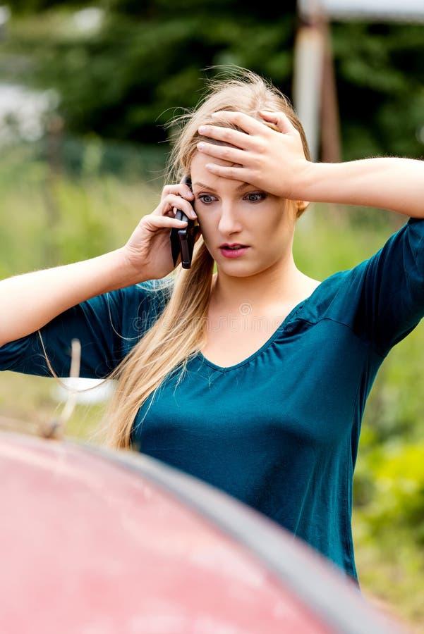 Frau, die ihr Telefon nach Autounfall wählt stockfotos