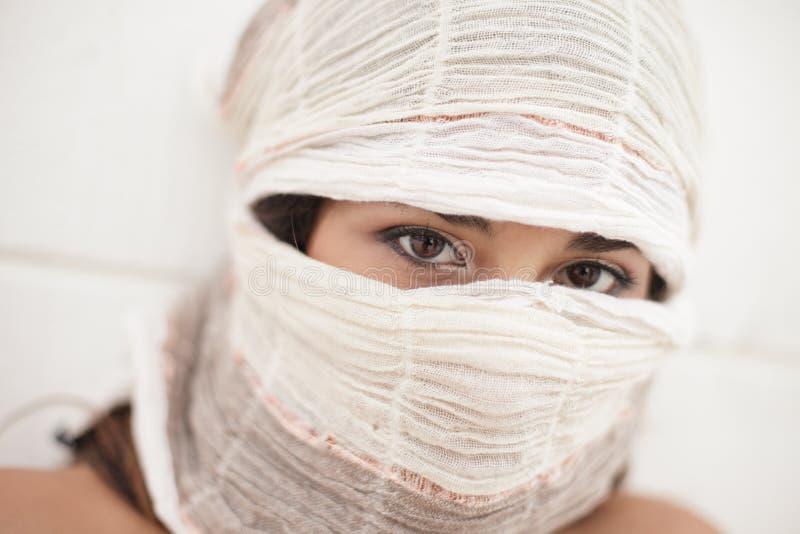 Frau, die ihre Augen aufdeckt stockfotografie