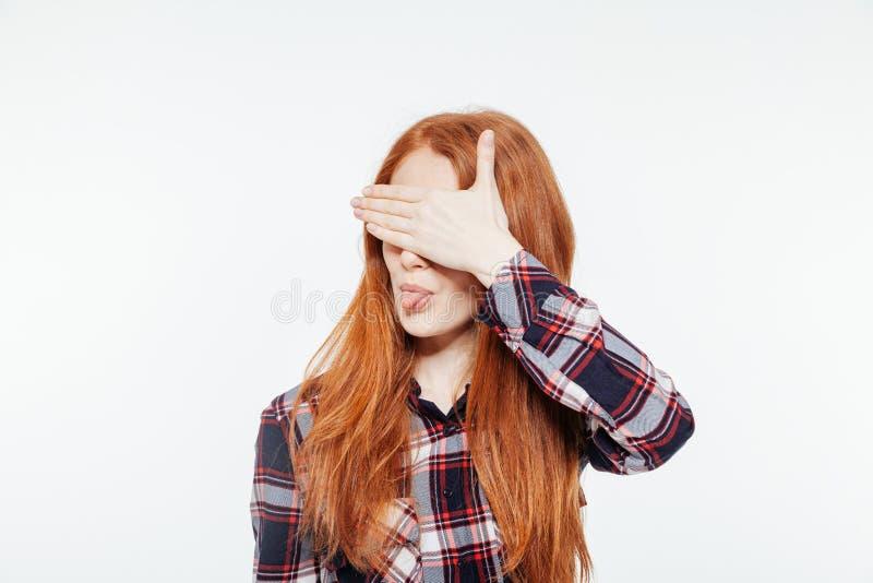 Frau, die ihre Augen bedeckt und Zunge zeigt lizenzfreies stockbild