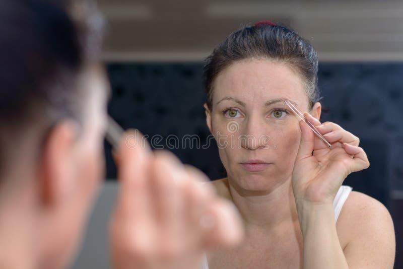Frau, die ihre Augenbrauen mit Pinzette zupft lizenzfreie stockfotos
