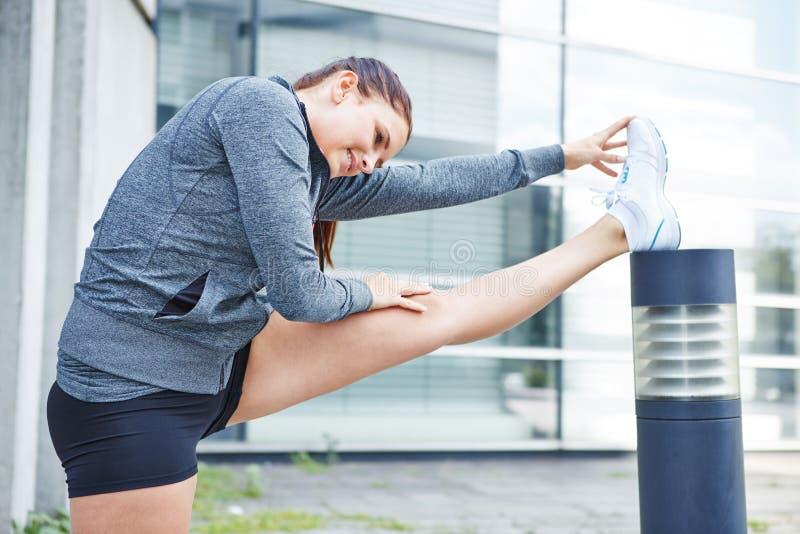 Frau, die ihre Beine bevor dem Laufen ausdehnt stockfoto