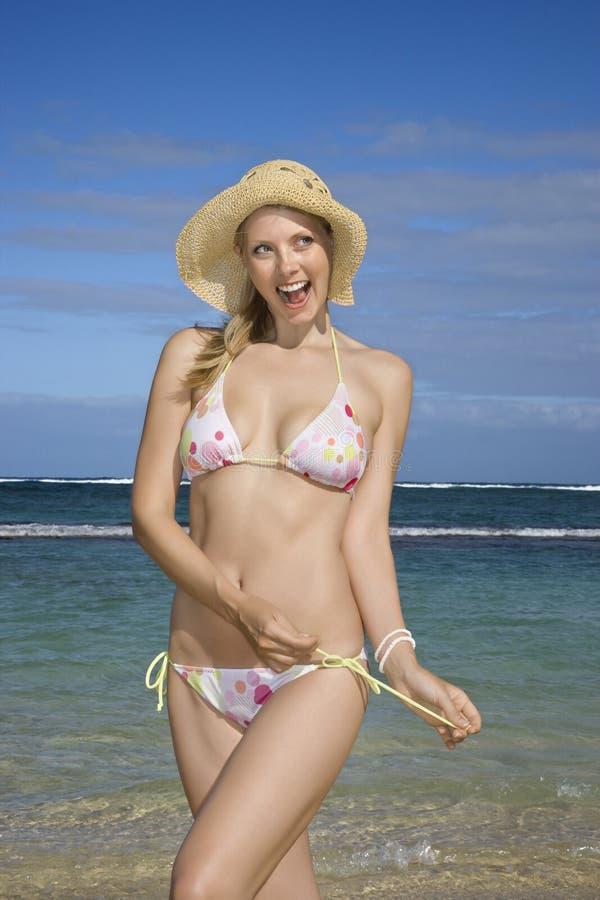 Frau, die ihre Bikinizeichenkette löst. stockfotografie