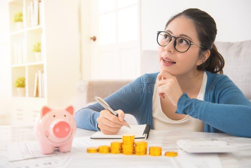 Frau, die ihre Einsparungen träumt und notiert stockfotos