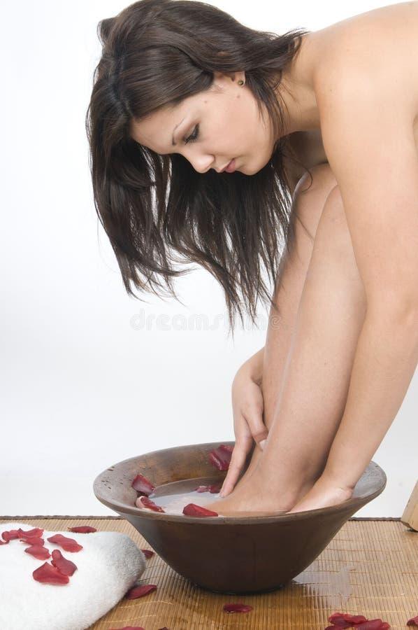 Frau, die ihre Füße mit Rosen im Badekurort wäscht lizenzfreies stockbild