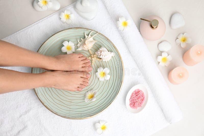 Frau, die ihre Füße in Platte mit Wasser, Blumen und Muscheln auf weißes Tuch, Draufsicht setzt lizenzfreie stockfotos