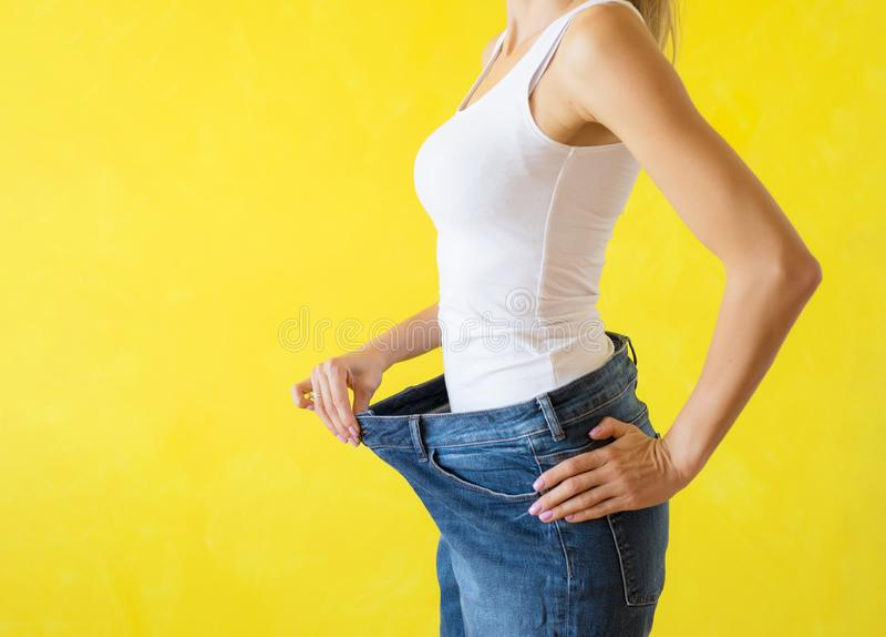 Frau, die ihre große Hose nach erfolgreicher Diät und Gewichtsverlust zeigt lizenzfreie stockfotografie