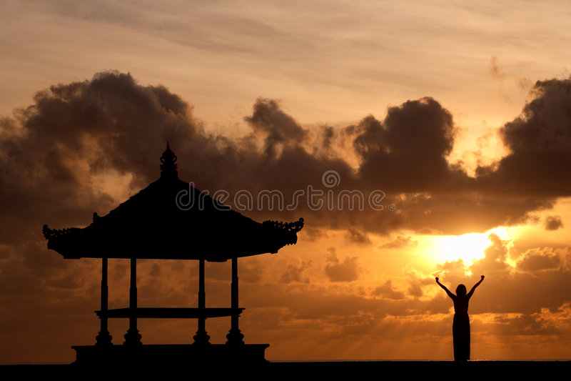Frau, die ihre Hände am Sonnenaufgang anhebt stockbild