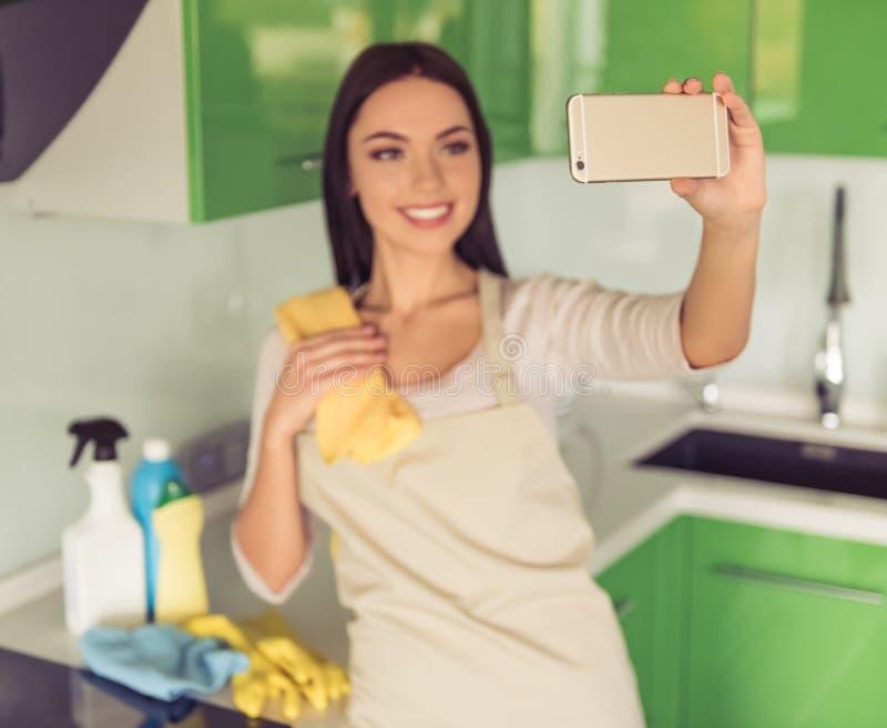 Frau, die ihre Küche säubert stockfotografie