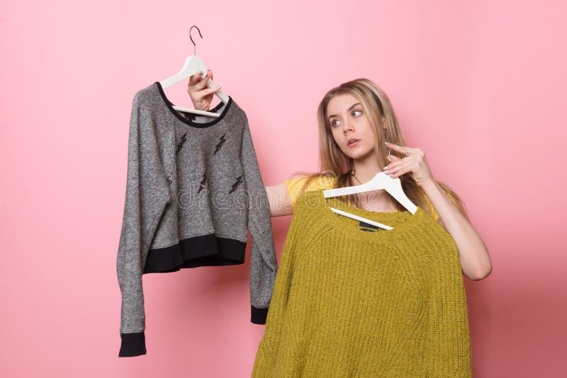 Frau, die ihre Modeausstattung wählt Mädchen, das was denkt, nach dem Einkaufen zu tragen stockfotos