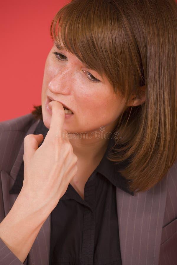 Frau, die ihre Nägel beißt stockbild