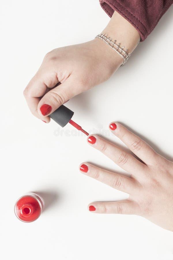 Frau, die ihre Nägel im Rot malt Über Ansicht lizenzfreie stockfotografie