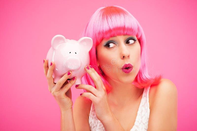 Frau, Die Ihre Piggy Querneigung überprüft Lizenzfreie Stockfotografie