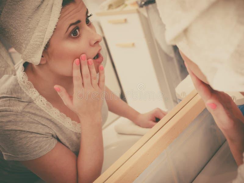 Frau, die ihre Reflexion im Spiegel betrachtet lizenzfreie stockfotografie