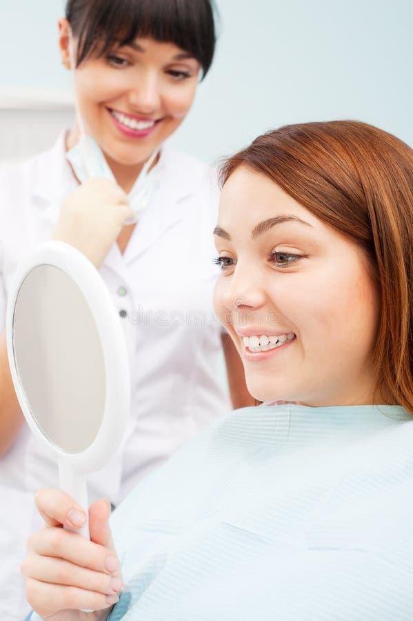 Frau, die ihre schönen Zähne betrachtet stockfotografie