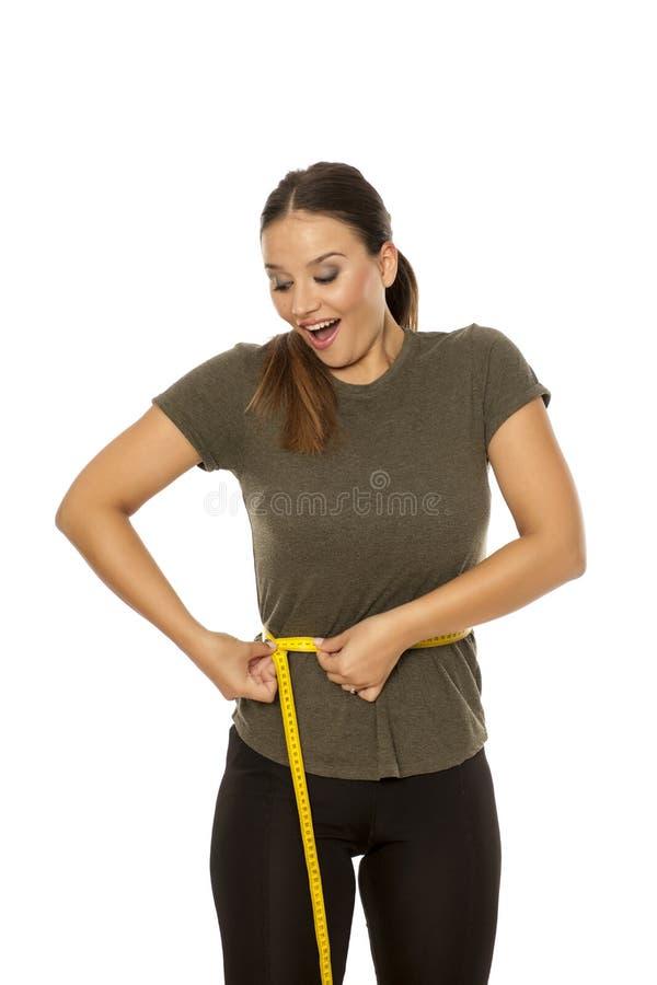 Frau, die ihre Taille misst lizenzfreie stockfotografie