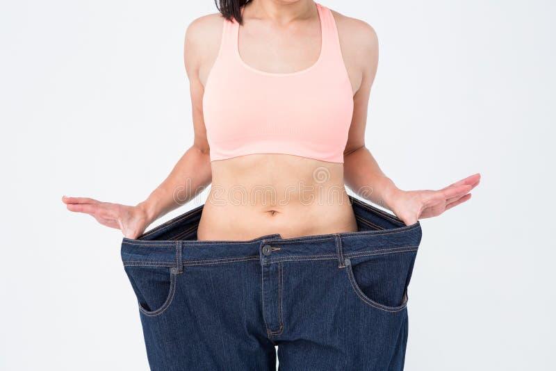 Frau, die ihre Taille nach verlierendem Gewicht zeigt lizenzfreie stockfotos