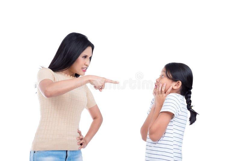 Frau, die ihre Tochter über weißem Hintergrund schilt stockfoto