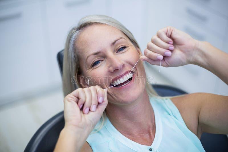 Frau, die ihre Zähne Flossing ist stockfotografie