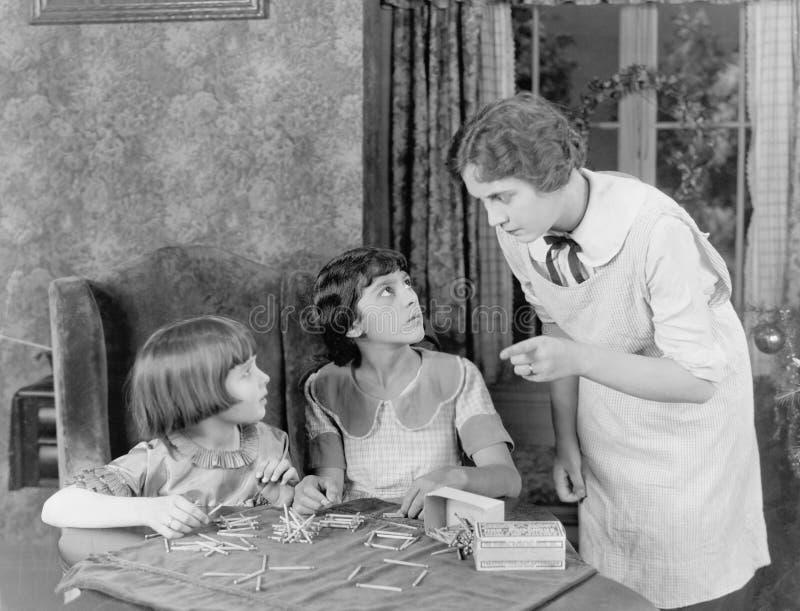 Frau, die ihre zwei Töchter für das Spielen mit Matchsticks schilt (alle dargestellten Personen sind nicht längeres lebendes und  lizenzfreies stockfoto