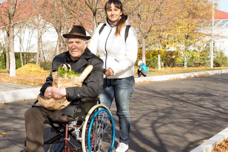 Frau, die ihrem älteren behinderten Vater hilft lizenzfreies stockfoto