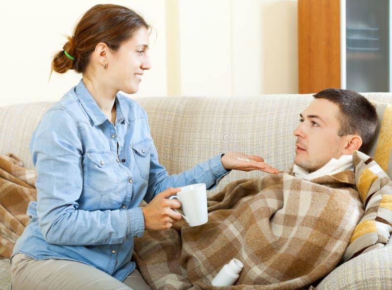 Frau, die ihrem Ehemann Tabletten gibt stockbild