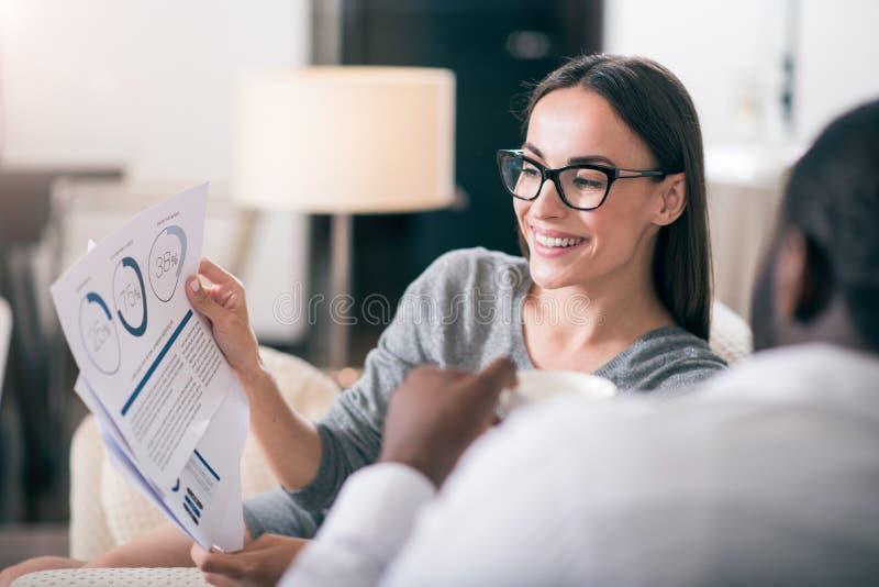 Frau, die ihrem Kollegen Diagramm zeigt stockbilder