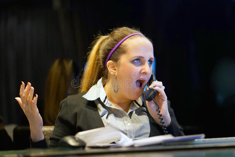 Frau, die an ihrem Schreibtisch bearbeitet und beantwortet einen Telefonanruf sitzt stockfotos