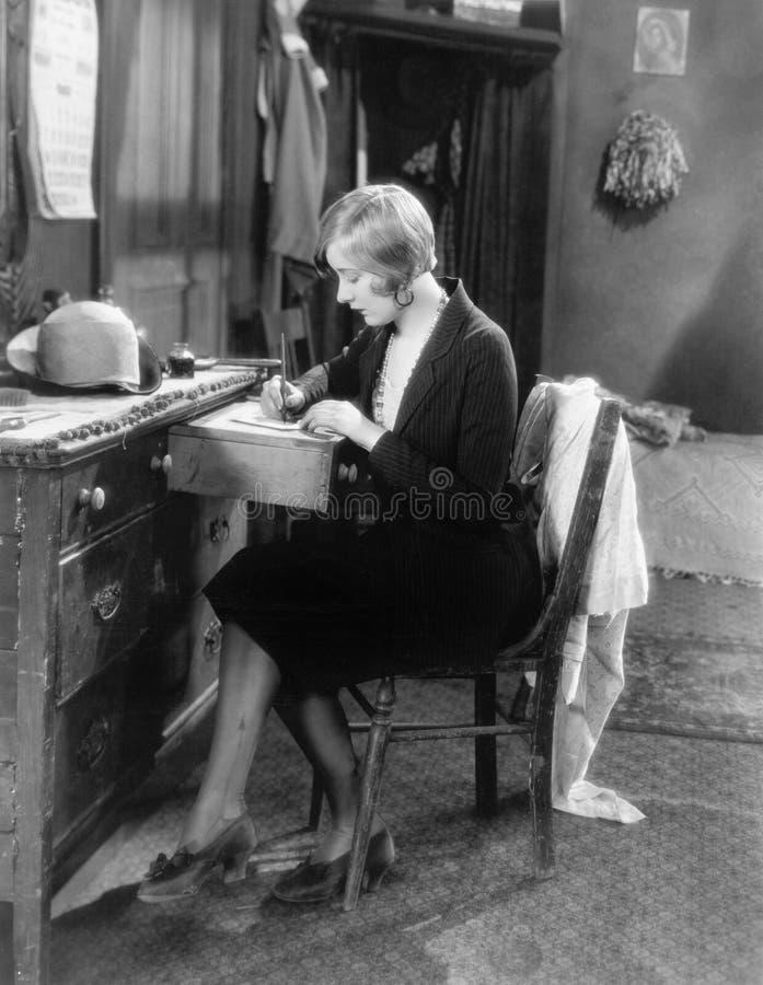Frau, die an ihrem Schreibtisch schreibt einen Brief sitzt (alle dargestellten Personen sind nicht längeres lebendes und kein Zus stockbild