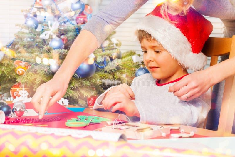Frau, die ihrem Sohn hilft, Feiertagsverzierung zu verzieren lizenzfreies stockfoto