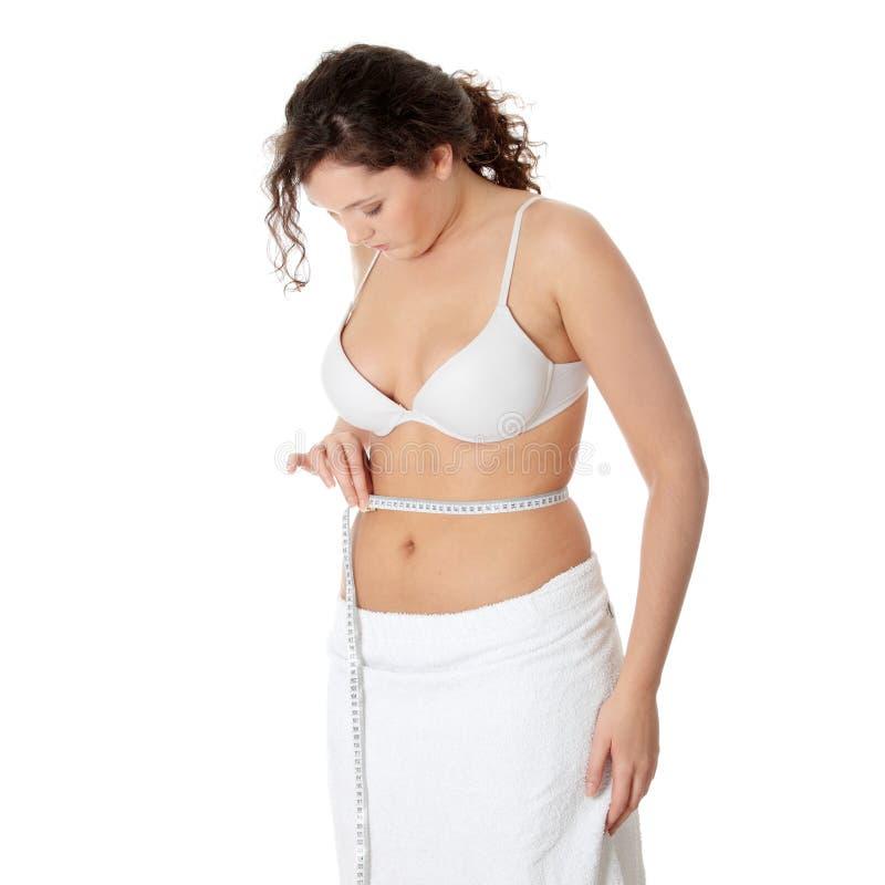 Frau, die ihren Bauch misst lizenzfreie stockfotos
