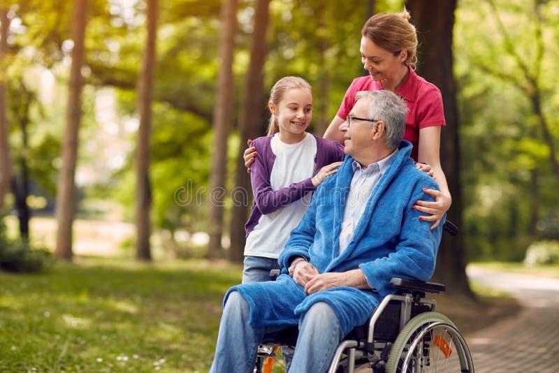Frau, die ihren behinderten Vater im Rollstuhl mit granddaugh besucht stockfoto