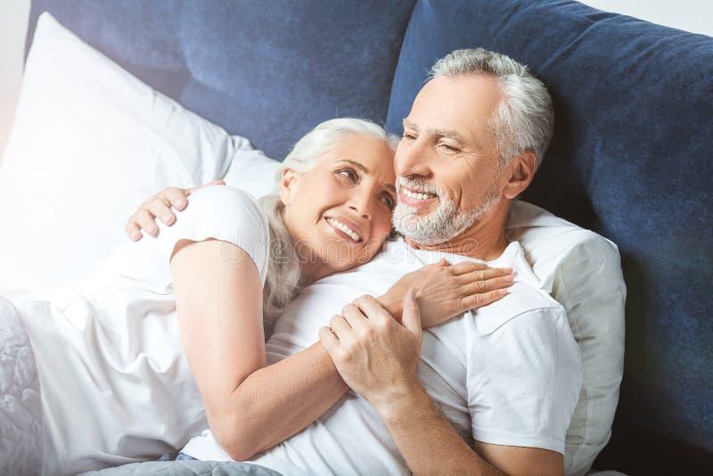 Frau, die ihren Ehemann umarmt stockbilder