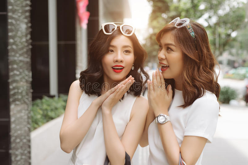 Frau, die in ihren Freundohren flüstert Zwei aufgeregtes Freunde shoppi stockfoto